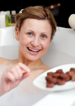 Happy woman eating chocolate while having a bath