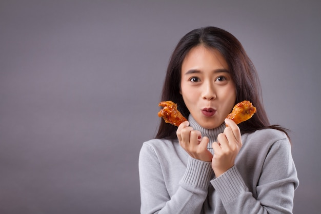 Happy woman eating fried chicken