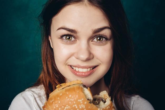 Happy woman eating a hamburger