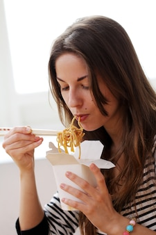 Счастливая женщина ест лапшу