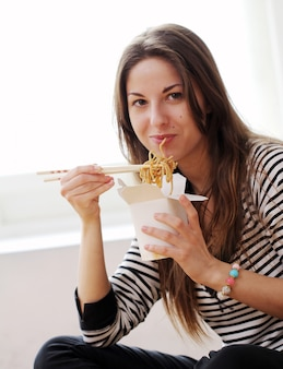 Happy woman eating noodles