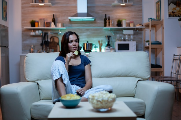 Happy woman eating popcorn on sofa and watching tv in living room at home. excited, amused, lonely lady enjoying the evening sitting on comfortable couch dressed in pajamas in front of television.
