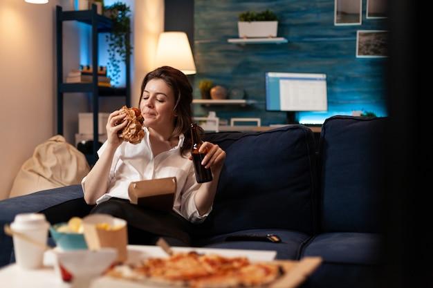 Donna felice che mangia un gustoso e delizioso hamburger di consegna che si rilassa sul divano guardando un film comico
