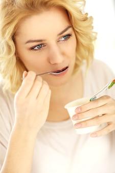 家でヨーグルトを食べる幸せな女性