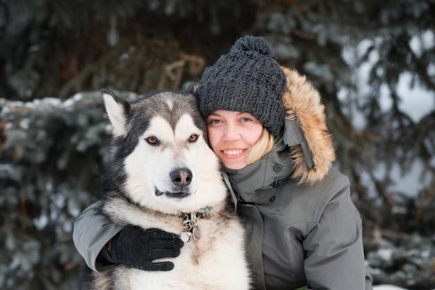 冬の森でアラスカンマラミュートを抱きしめる幸せな女性。閉じる。