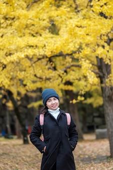 행복한 여성은 가을철에 야외 공원에서 즐거운 시간을 보내고, 코트와 모자를 쓴 아시아 여행자는 노란 은행나무 잎 배경을 배경으로 합니다.