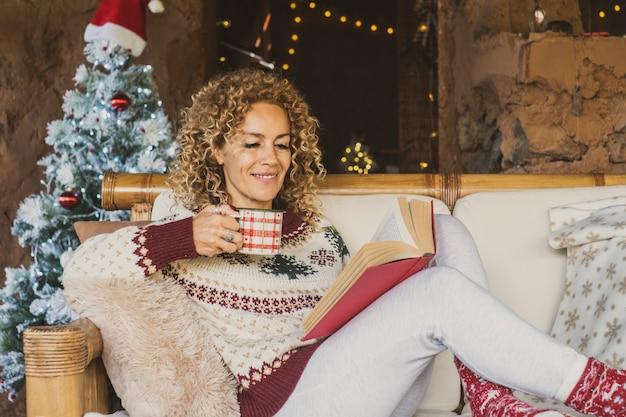 幸せな女性はソファで自宅でリラックスしてクリスマス休暇をお楽しみください