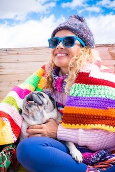 행복한 여성은 다채로운 덮개로 겨울에 야외 집에 앉아 있는 퍼그 개를 즐깁니다 - 부드러움과 우정 사람들 동물 개념 생활 방식 - 쾌활한 예쁜 여성 미소 초상화