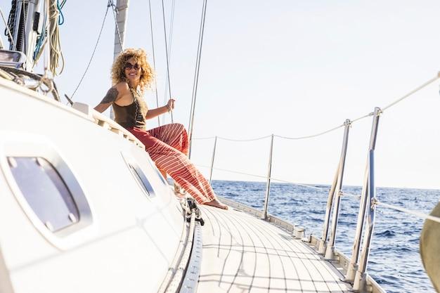 Счастливая женщина наслаждается путешествием на парусной лодке, сидя на лодке с океаном вокруг