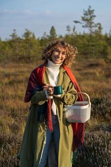 행복한 여성은 시골에서 따뜻한 차 한 잔을 들고 웃고 있는 따뜻한 가을날 화창한 날씨를 즐깁니다.