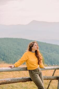 秋の自然を楽しむ幸せな女性美しい風景ライフスタイル旅行のコンセプト