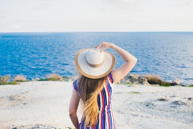 トロピカルブルーの水で夏に楽しくリラックスしたビーチを楽しんでいる幸せな女性。ビーチの日よけ帽をかぶって旅行で幸せな美しいモデル。 Premium写真