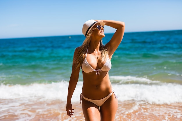 Happy woman enjoying beach relaxing joyful in summer by tropical blue water