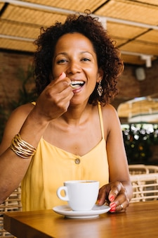 Happy woman enjoying the cappuccino coffee in the caf�