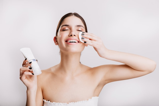 Happy woman enjoying facial spa. model cleans face with sponge before applying cream.