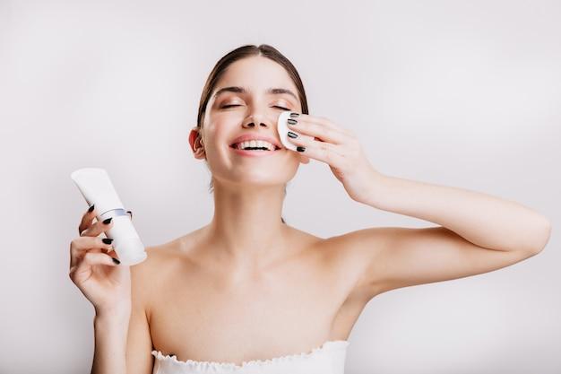 얼굴 스파를 즐기는 행복 한 여자. 모델은 크림을 바르기 전에 스폰지로 얼굴을 닦습니다.