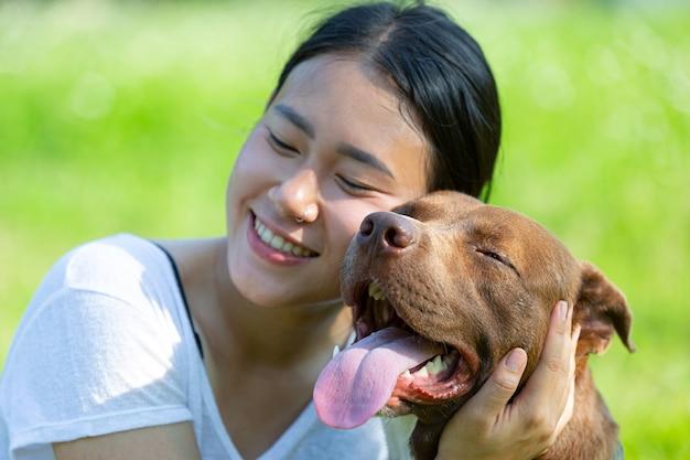 Happy woman enjoying her favorite dog in the park. Premium Photo