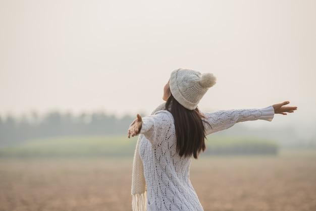 Счастливая женщина наслаждается идиллической природой, празднует свободу и поднимает руки