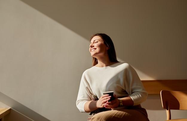 カフェで朝のコーヒーを楽しんで幸せな女性