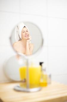 거울 앞의 화장실에서 아침 피부 관리 루틴을 즐기는 행복 한 여자 샤워 후 아침 피부 관리 루틴을 하 고 행복 한 젊은 여자
