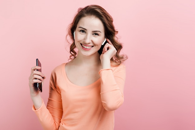 Happy woman enjoying music in airpods  with pink wall