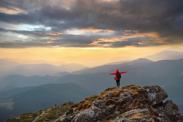 山で自然を楽しんで、上げられた手で空を見ている幸せな女性