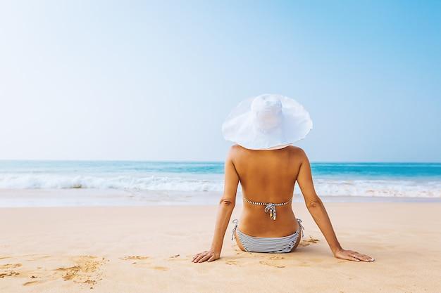 ビーチで海の景色を楽しみ、夏の日にリラックスして幸せな女性。