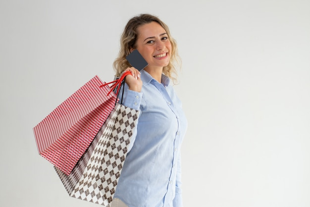Happy woman enjoying shopping and paying with credit card