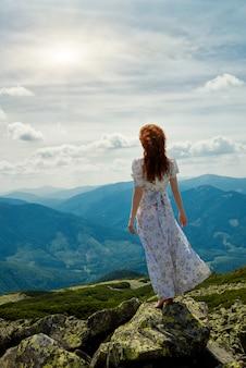 Счастливая женщина, наслаждаясь природой в горах
