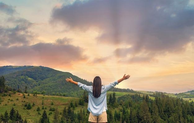 산 꼭대기에 서있는 동안 일몰을 즐기는 행복한 여자