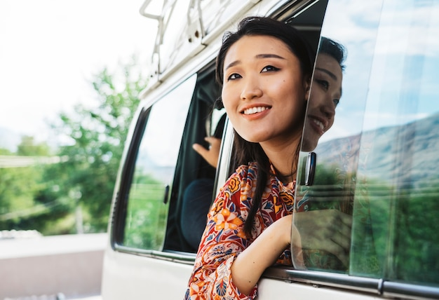 Happy woman enjoying the view from a van