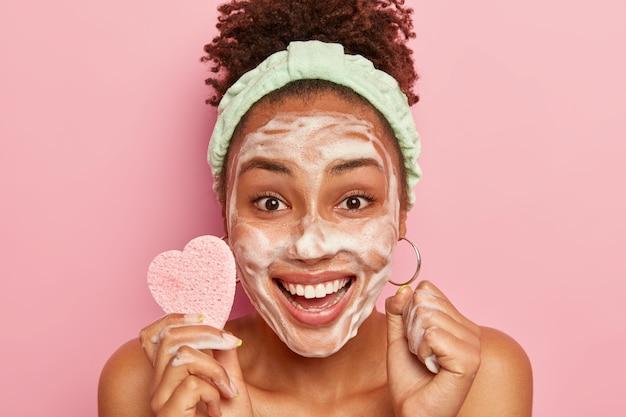 幸せな女性はリラックスした時間を楽しんで、シャボン玉で顔を洗い、さわやかで喜びを感じ、顔色を拭くための化粧用スポンジを持っています