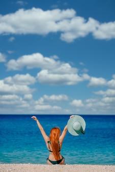 행복 한 여자는 열정적으로 해변에 앉아 그녀의 손을 올립니다