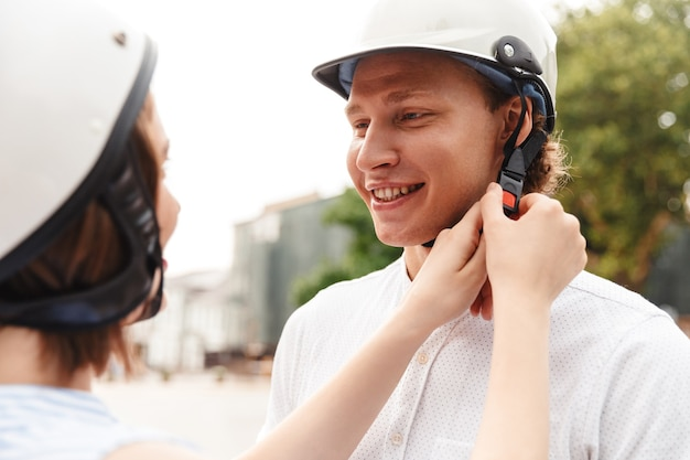 Happy woman fastens a helmet to her boyfriend outdoors