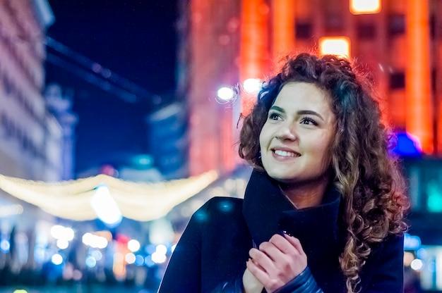 Счастливая женщина чувство городской рождественские вибрации в ночное время. счастливый женщина, глядя вверх с рождественский свет в ночное время
