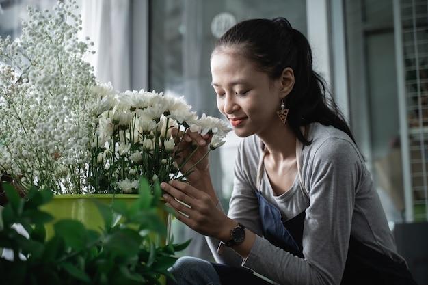 美しい花束の香りがするエプロンを身に着けている幸せな女性の花屋