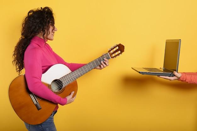 Happy woman follows a guitar lesson online.