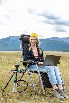 행복한 여성 프리랜서가 산에서 인터넷을 사용하여 앉아서 노트북 작업을 하고 있습니다.