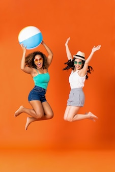 Happy woman friends in casual summer clothes jumping