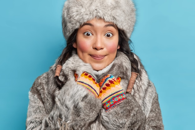 Happy woman from alaska looks with surprised delighted face at front wears winter hat fur coat and mittens poses against blue wall