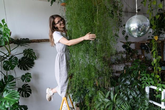 가정의 아늑한 정원 취미 개념에서 아스파라거스 관엽식물을 껴안는 행복한 여성 정원사