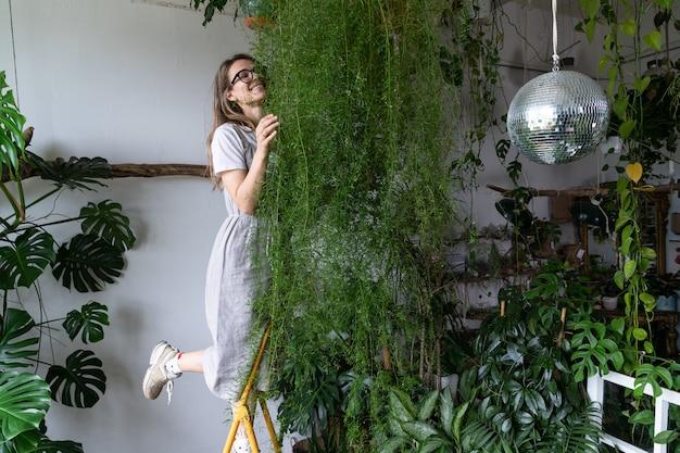 Happy woman gardener embracing asparagus houseplant at home indoor cozy garden hobbies concept