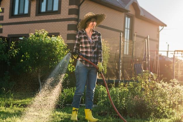 晴れた暖かい夏の日に彼女の菜園のベッドに水をまく作業服を着た幸せな女性の庭師。あなたの農場の菜園で働くことの概念