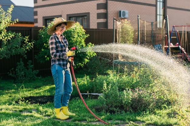 日当たりの良い暖かい夏に彼女の菜園のベッドに水をまく作業服で幸せな女性の庭師
