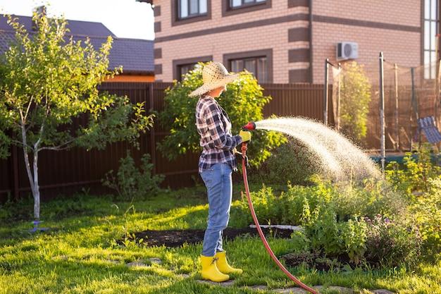 그녀의 야채 정원에서 침대에 물을 작업복에 행복 한 여자 정원사
