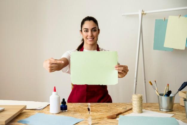 Donna felice che gesturing mentre tenendo carta fatta a mano