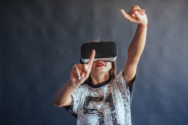 Happy woman gets experience of using vr-glasses virtual reality headset.