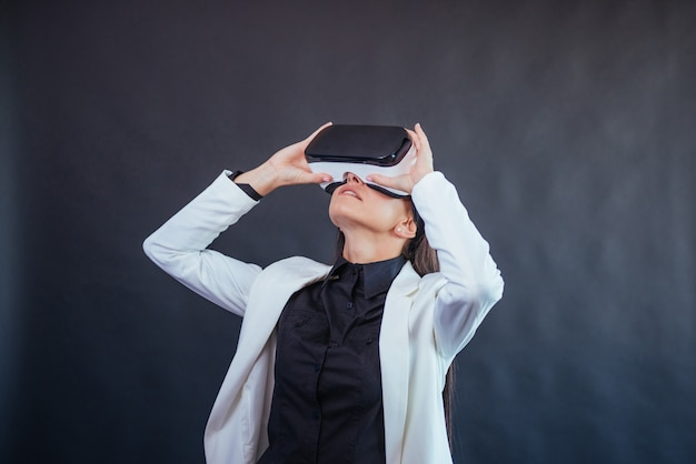 Happy woman gets the experience of using vr-glasses virtual reality headset.