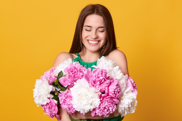 Happy woman gets flowers from husband, looking at her present with charming smile