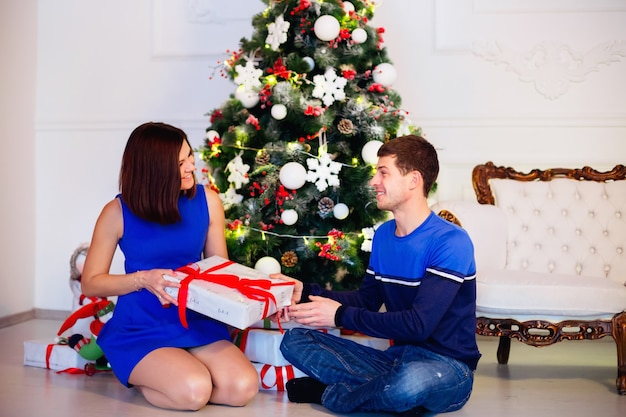 Happy woman gets her christmas present from her husband. nice couple sitting with gifts near christmas tree